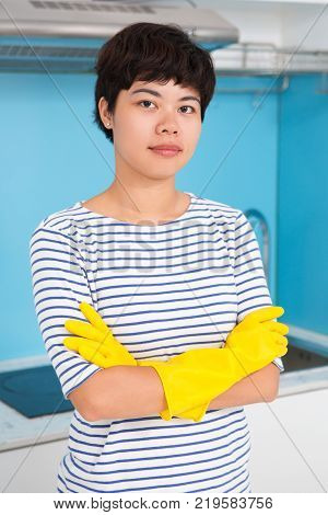 Confident Asian female cleaner looking at camera and ready to make kitchen tidy. Serious attractive housewife in rubber gloves crossing arms on chest. Housekeeping concept