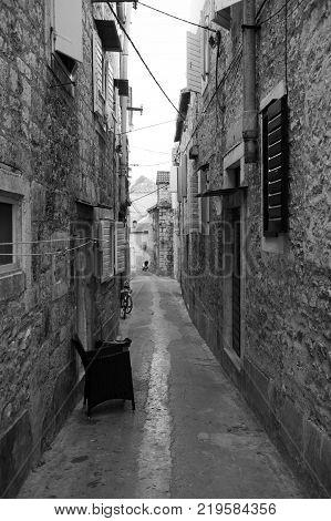 Old narrow stone street inside Milna old town, Croatia.