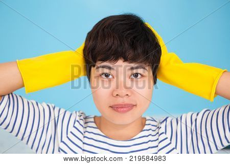 Unsmiling Asian housewife holding head in hands and looking at camera. Amazed young woman in rubber gloves knowing about new detergent. Cleaning concept