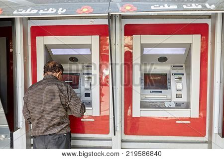 Yazd Iran - April 22 2017: An elderly Iranian man uses an ATM to withdraw cash from a national payment card of Iran.