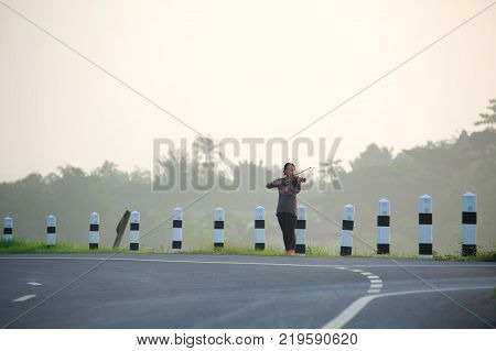 an asian woman is playing violin on the road side in the morning with soften fog