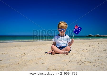 Cute child with Australian flag sitting on the sand at the beach on Australia day
