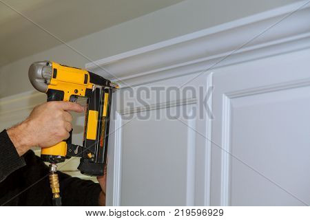 Wood working using brad nail air gun to Crown Moulding on white kitchen cabinets framing trim, with the all power tools