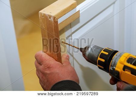 Assembling furniture from chipboardsnd drills the cabinet door, using a cordless screwdriver, close up.