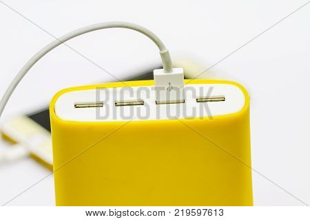 Yellow USB portable charger device for cellphone with four usb ports isolated on white background