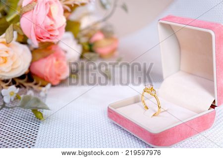 Golden ring with diamonds in jewelry box decorate with flower. Concept wedding, Love, Valentine's day, Happy Birthday. Gift.