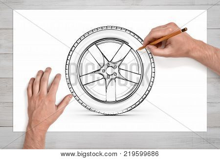 Two male hands in close view as they draw a car tire with a pencil on white paper. Business plans. Car design. Product development.