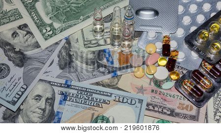 a lot of medical pills in different colors and capsules on a dollar bills top view