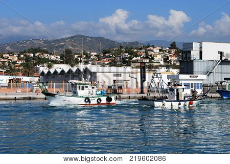 CALETA DE VELEZ, SPAIN - OCTOBER 27, 2008 - Traditional fishing boats entering the harbour with buildings to the rear Caleta de Velez Malaga Province Andalusia Spain Western Europe, October 27, 2008.
