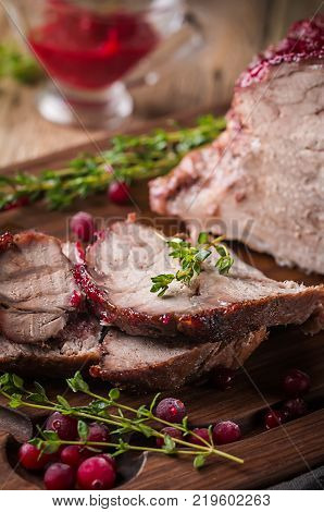 Baked pork meat with cranberry sauce and thyme over wooden background. Concepts of holiday food.