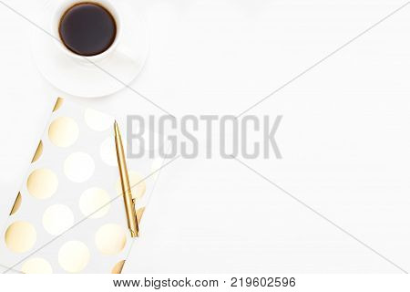 A cup of coffee and a notebook of gold color on a white background. Coffee break