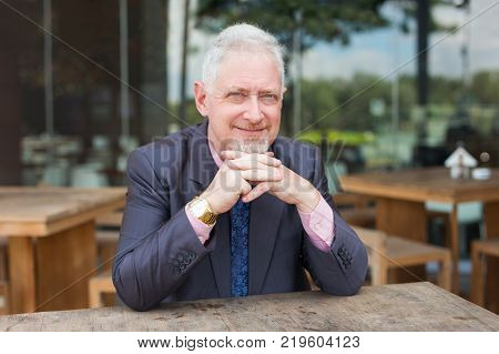 Closeup portrait of content senior handsome man looking at camera with his hands clasped and sitting at table in outdoor cafe