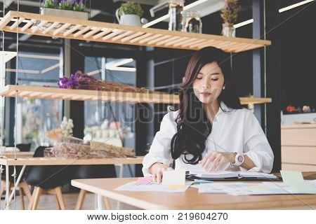 asian businesswoman with notebook at workplace. startup woman working with business plan report document at office.  young female entrepreneur analyze accounting market data. financial adviser with paperwork on table.