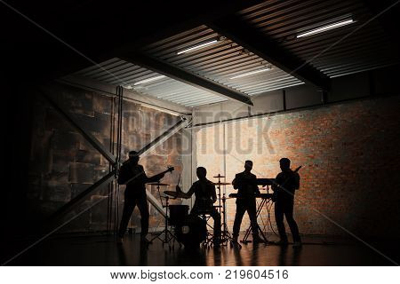 Bands silhouettes with on a concert. Music band and fashion. Handsome young men in suits playing rock and singing song.