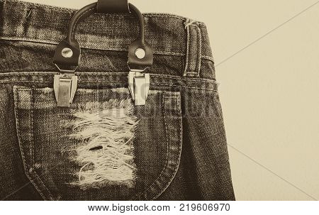 Detail of a white suspenders on vintage jeans close-up