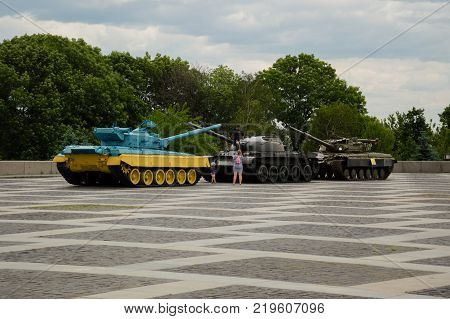 KYIV, UKRAINE - JUNE 1, 2017, Young family making photo on the one of three panzers standing on the Motherlands square in Kyiv. One of the panzers is painted in national Ukrainians colours