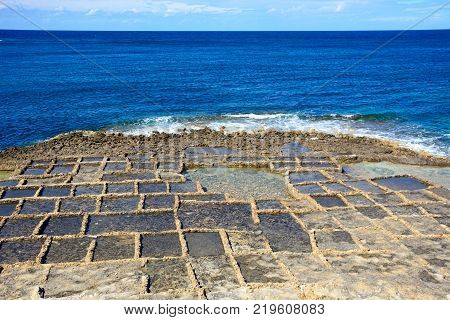 Salt pans along the waterfront with views out to sea Redoubt Marsalforn Gozo Malta Europe.