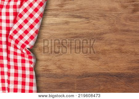 Red tablecloth on wooden background.Napkin tablecloth on old wood