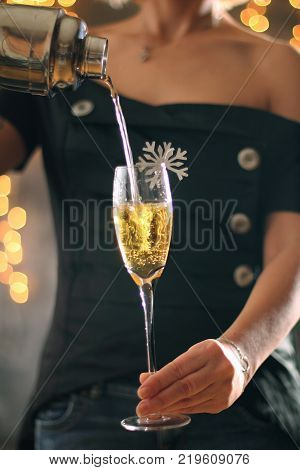 A girl pours a drink on a holiday. Christmas concept