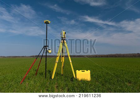 Surveyor equipment outdoors theodolite on tripod and gps, blue sky in background