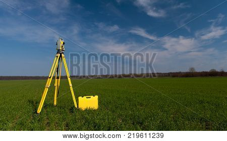 Surveyor equipment outdoors theodolite on tripod, blue sky in background
