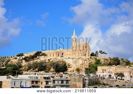 MGARR, GOZO, MALTA - APRIL 3, 2017 - View of Our Lady of Lourdes church on the hillside overlooking the town Mgarr Gozo Malta Europe, April 3, 2017.