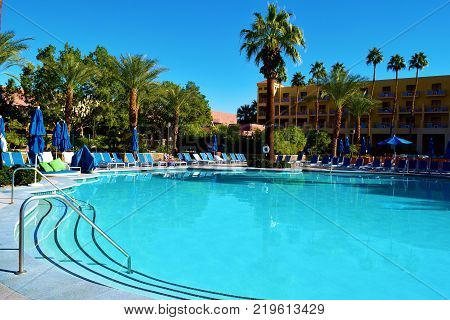 December 18, 2017 in Palm Springs, CA:  Large swimming pool within a courtyard taken at the Renaissance Hotel in Palm Springs, CA where guests can sunbathe and go swimming surrounded by beautiful desert gardens