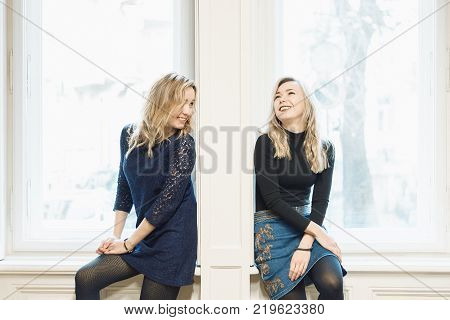 Two blonde female friends chatting and laughing while sitting by the wall between two windows. Breaking down the barrier between people concept