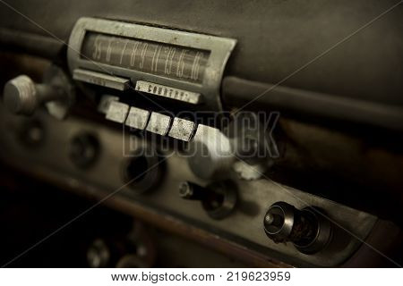 close up of old push button radio in dashboard of old junk vintage car