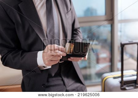 Money in wallet. Tender senior businessman hands searching for credit car in the black leather wallet on the blurred background