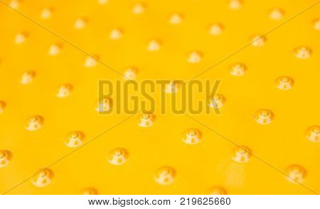 Detail of micro metallic grill tractor part painted in yellow with multiple hexagonal shapes for ventilation and hot air exhaust