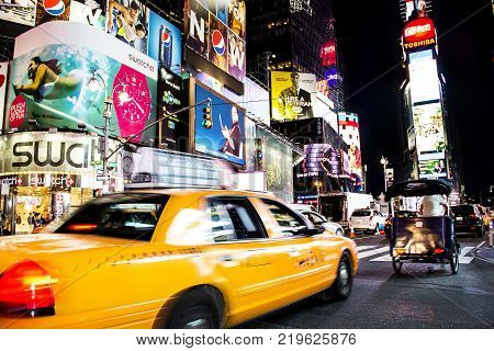 Times Square, New York City, New York, United States - circa 2014 - taxi cab driving in motion blurry times square night new york city with play marquees and brightly lit advertising signs and lots of people