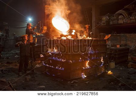Wenzhou, China - July 18, 2017: Foundry worker pouring hot metal into cast. Molten metal. Left over material from the steel manufacturing process is poured away on at a Steel Foundry