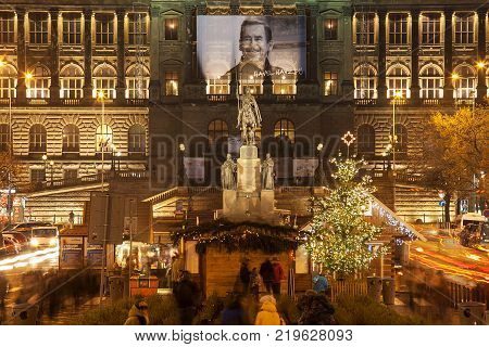 Prague, Czech Republic - December 07, 2014: Traditional christmas market under ther Historical statue of saint Wenceslas on top of Wenceslas square and national museum in background with portrait of Vaclav Havel by night. Prague, December 07, 2014
