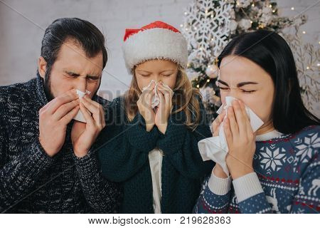 Family is sick at Christmas They have handkerchief. Sick people have runny nose. Merry Christamas and Happy New Year .