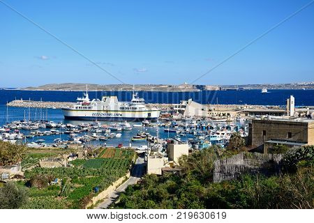 MGARR, GOZO, MALTA - APRIL 3, 2017 - Fishing boats and yachts moored in the harbour with the Gozo ferry moored in the port to the rear and agricultural fields in the foreground Mgarr Gozo Malta Europe, April 3, 2017.
