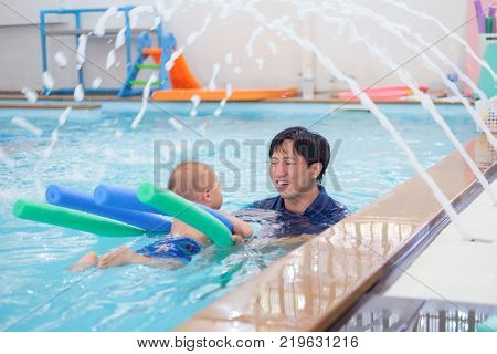Asian Father take Cute little Asian 18 months / 1 year old toddler baby boy child to swimming class in Thailand Happy infant enjoying his first swim in pool with his dad Selective focus at dad face