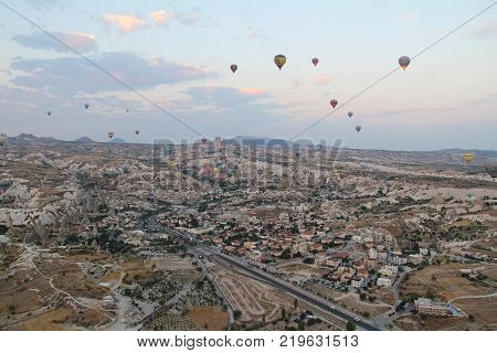 Goreme Cappadocia Turkey - August 16 2017: Beautiful view of the village of Goreme with balloons flying over it at sunrise. One of the sights of Turkey. Tourism travel beautiful landscapes nature. Awesome landscape.