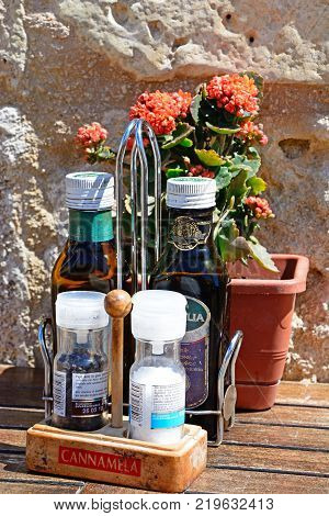 GOZO, MALTA - APRIL 3, 2017 - Salt pepper olive oil and vinegar with flowers to the rear on a wooden table within the citadel Victoria (Rabat) Gozo Malta Europe, April 3, 2017.