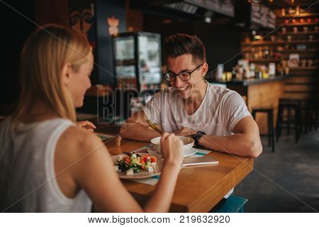 Happy young couple in love having a nice date in a bar or restaurant. They telling some stories about them self , drinking tea or coffee and eating salad and soup