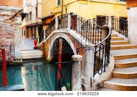 Canal in Venice, Italy and colorful buildings with a pedestrian bridge.