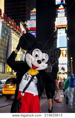 Times Square, New York City, New York, United States - circa 2015 -  disney mickey mouse character in costume waving to the camera in times square at night new york city