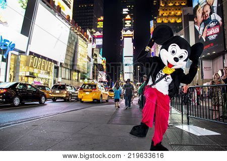 Times Square, New York City, New York, United States - circa 2015 -  disney mickey mouse character in costume times square at night new york city