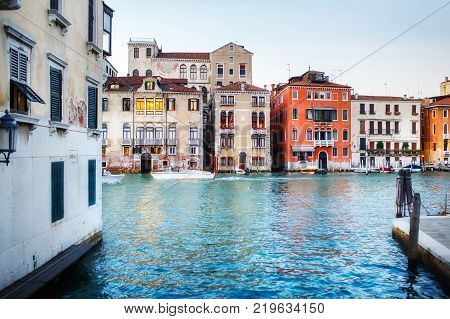 Boats moored between colorful houses and boats floating along the canal. Venice, Italy.