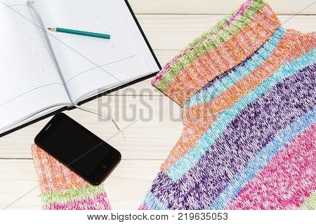 knitted sweater, laptop, smartphone top view Women's clothing