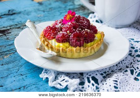 Tartlet With Fresh Raspberries And Spoon On Blue.tartlet With Fresh Raspberries And Spoon On Blue.ta