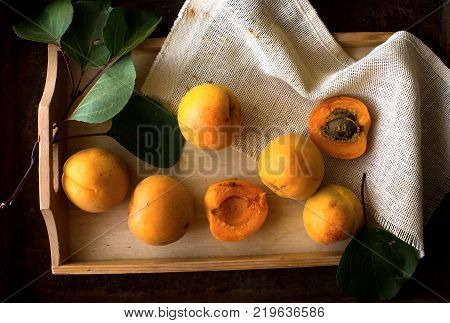 Apricots And Its Cross-section On The Old Wooden Table. Flat Lay. Apricots And Its Cross-section On
