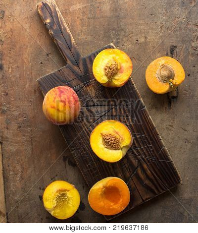 Fresh Organic Peaches on rustic wooden background with copy space. Sweet summer peaches.