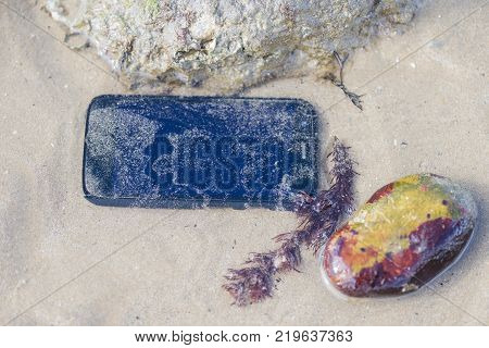 Mobile phone submerged in the water of the beach