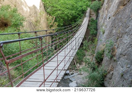 Wide angle of Iron and wooden suspension bridge in canyon